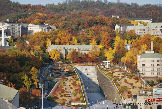 Aerial view of Ewha University in Seoul, showing the stone buildings amongst orange, red and yellow autumnal trees. Landscaped gardens to the front of the frame.