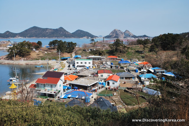 View over the rooftops on Seonyudo island, multicolored roofs next to a secluded bay, in the background are mountains and sea.