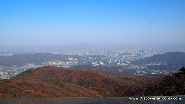 A view from Cheonggyesan mountain, over foothills covered in fall color, to a soft focus cityscape in the background.