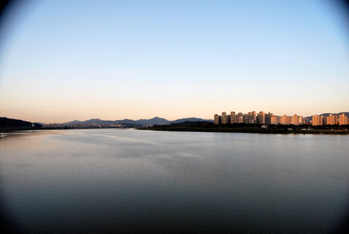 Wide angle view over the Hangang river with the city in the distance, soft evening light and mountains in the far background.