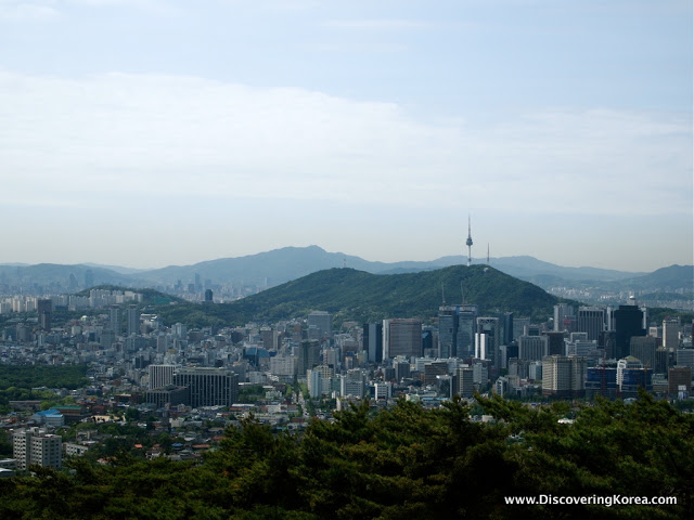 View over Seoul with the tower in the center of the frame, mountains in the background and cityscape.