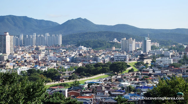 Suwon view of tall buildings, interspersed with low housing, with mountains in the background.