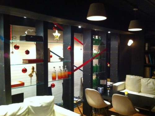 Interior of a bar, with black and glass cabinetry, cream and black furniture, red and green bottles in the background.