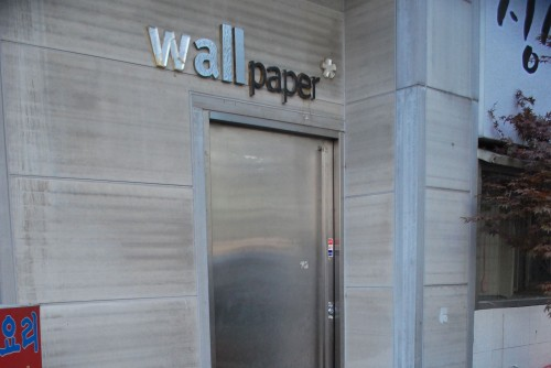 View of an entrance to a bar, a stone block building with a metal door and a sign above it saying wall paper in metallic lettering.
