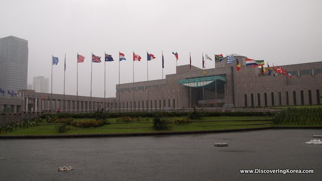 Exterior view of the brick War Memorial of Korea building in Seoul. Flags from many different nations are flying, on a cloudy and wet day.