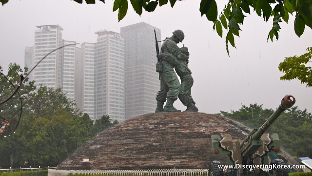 A stone dome, with a bronze statue of two soldiers embracing, a cannon in the foreground, and skyscrapers in the background.