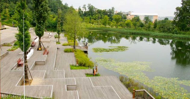Geometric steps with bench seating, ornamental trees, leading down to the lake at West Seoul Lake Park. The clear water of the lake reflects the trees and grasses in the background that surround it.