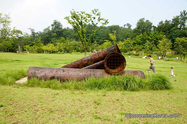 Three large metal rusting pipes in the middle of a grass lawn with trees and shrubs in the background and a man and a child running in the background.