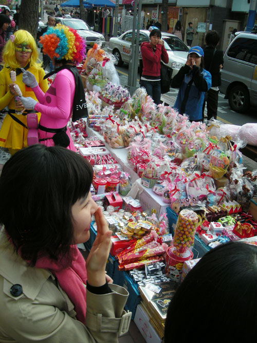 A table, laden with candy, in the street, for White Day in Korea. Two colorfully dressed people with multicolored wigs on the left of the frame, and other pedestrians around the table.