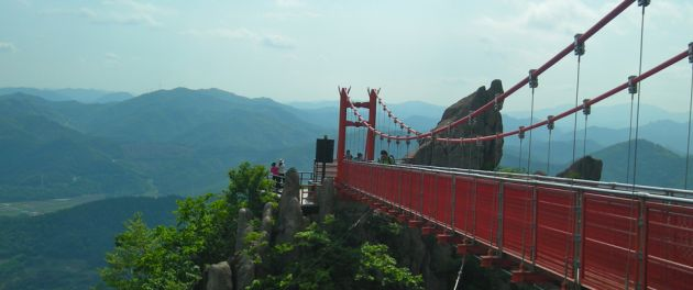 A view across a red footbridge towards soft focus mountains at Wolchulsan National Park.