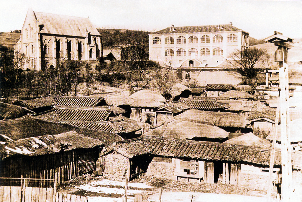 An old sepia photo, showing a large Catholic Church in the top left of the frame, and a large warehouse type building next to it. In front are a lot of small, traditional Korean homes, some looking run down.