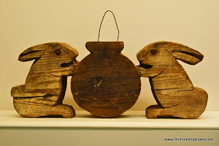 A wooden carving of two rabbits on either side of a round pot. The wood is dark brown, on a light colored surface.