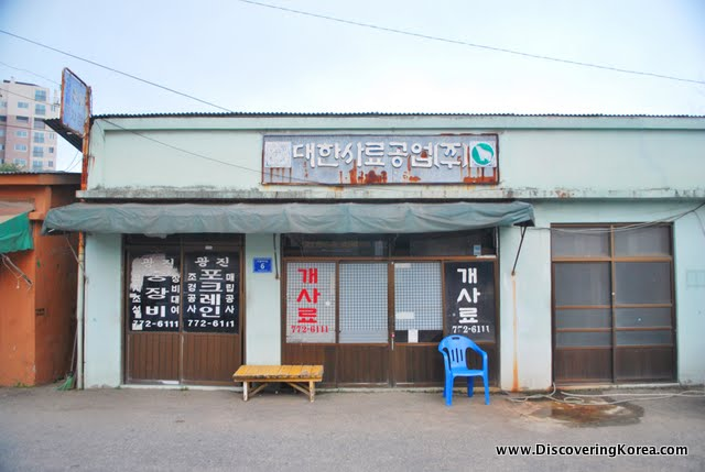 Shop front with a chair and low table outside, sign written in Korean.