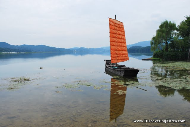 Traditional Korean sail boat moored in Yangsuri, with soft focus trees and reflecting mountains in the background.