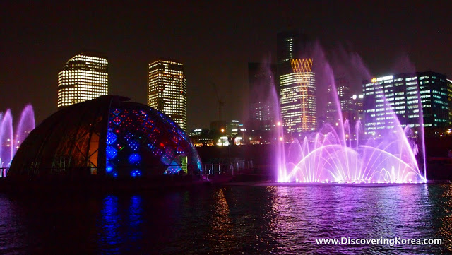 Night time cityscape of Yeouido island, as seen from a boat on the Hangang. Purple colored fountains, a multicolored dome and bright lights on the skyscrapers.