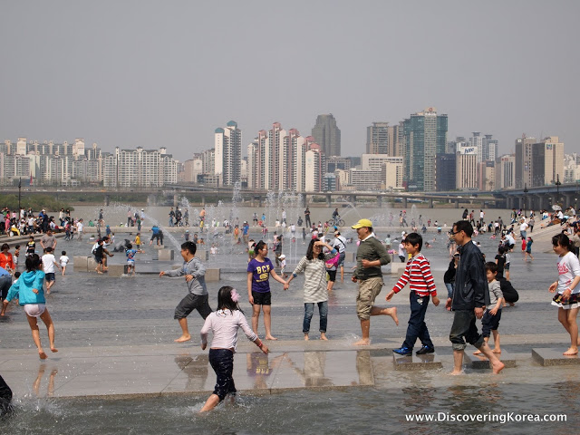 Children and adults playing in water and fountains, with a backdrop of skyscrapers, Yeouido island.