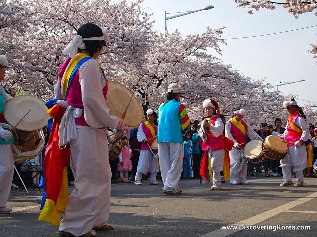 A group of traditionally dressed Koreans with drums, dancing in the street, lined with cherry blossom on Yeouido island.