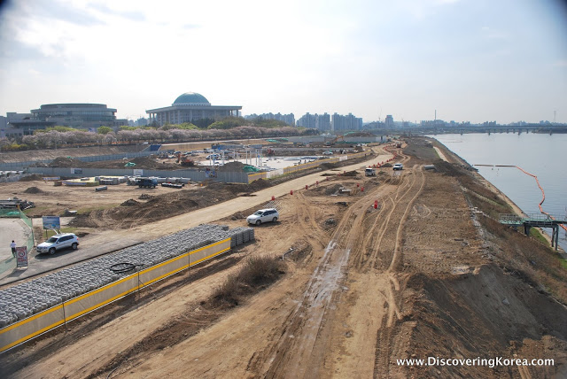 A construction site, with bare earth, the river to the right of the frame, construction machinery at work, building the Yeouido Hangang Riverside Park.