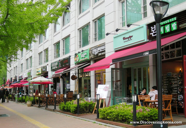 A row of shops and cafes with red awnings, red and white garden umbrellas and planters with low bushes.