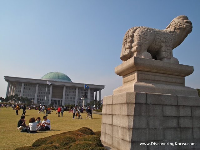 A stone plinth with a stone dragon statue on top, with a white stone building and green half moon roof behind. People sitting on the grass and walking around in the center of the frame.