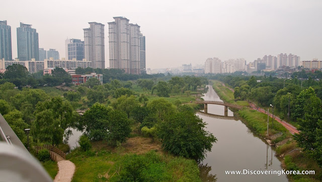 Elevated view of the river, with a pedestrian bridge, crossing between two very green and lush areas, with the city in the background at Yeouido Saetgang Park.