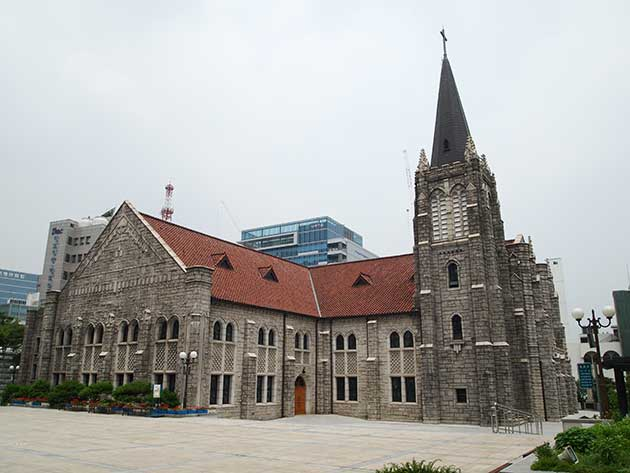Youngnak Presbyterian church in Seoul, an imposing building of stone and tile roof, arched windows and a tall spire.