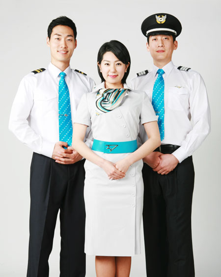 Three airline staff, two men dressed in white shirts, black pants and bright blue ties, one is wearing a Captain's hat. In the middle is a woman in a white dress with a bright blue sash and striped scarf.