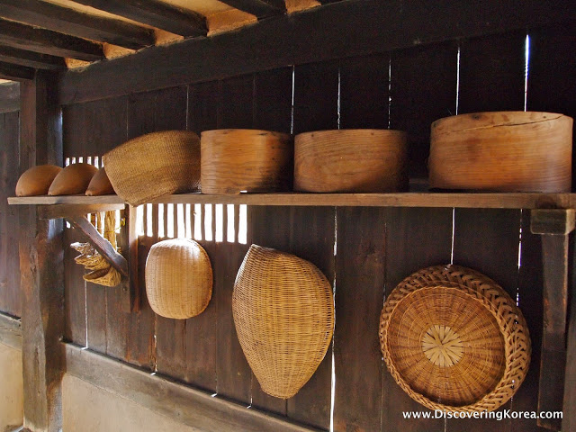 A shelf with wooden bowls and baskets, below it are baskets hung on the wooden wall at Andong Hahoe Folk Village.