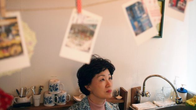 A woman in a room looking up with white and blue tea mugs behind her, a sink and tap in the background and postcards clipped to a line across the top of the frame.