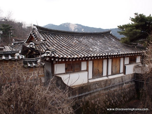 A traditional Korean house, with wood frame and white walls and the traditional curved roof. In the background is vegetation and mountains.