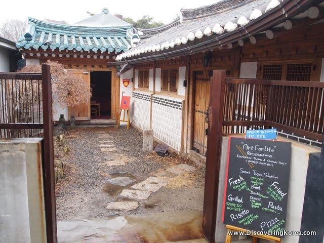 Looking through metal gates into a cafe courtyard in buam dong. To the right of the frame is a chalkboard with menu, to the left of the frame is the entrance through a wooden door. The building has a traditional curved roof.