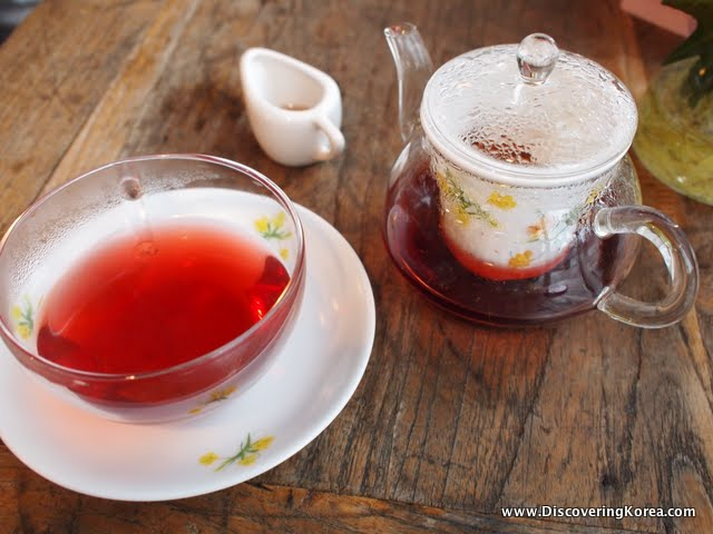 A close up of a glass cup, white saucer and glass tea pot containing hibiscus tea, on a wooden background.