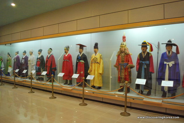 A glass fronted exhibit of traditional Korean clothing.