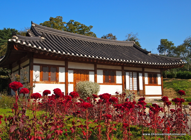 A traditional building painted white with wood beams and latticed shutters with a traditional curved roof. In the foreground are bright red plants, the background is trees and blue sky.