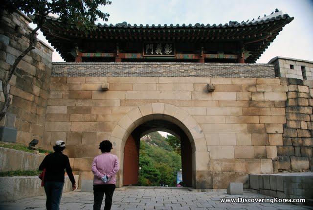 An imposing stone entrance gate, with a traditional curved roof, an archway with metal doors and a stone courtyard in front. Two people are walking towards the gate, with trees on the other side.