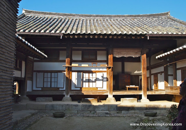 A house with a traditional curved roof, white walls and wooden pillars with a stone courtyard in the foreground and blue sky in the background.
