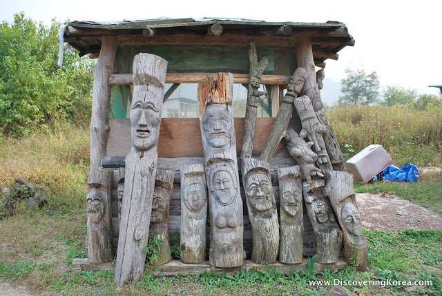 Traditional carvings, like totem poles at Andong Hahoe Folk Village, standing up against a small wooden building with shrubs in the background.