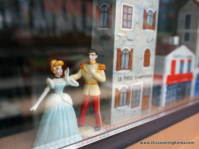 Looking into a glass cabinet containing figurines of a man and a woman and a model house.