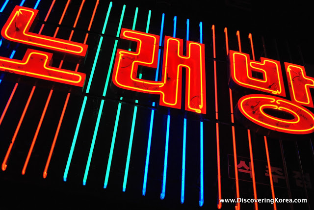 A close up of a neon sign with Korean lettering lit up in red and stripes of blue, green and red running vertically through it on a black background.
