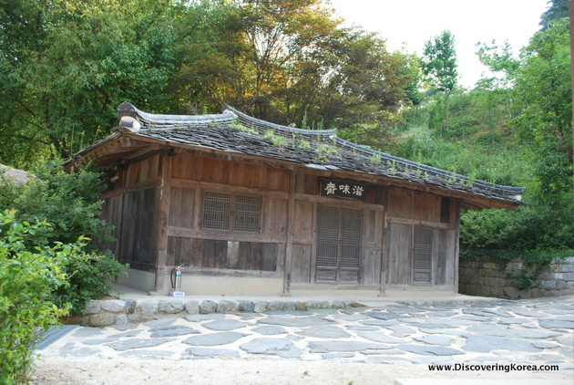 An old wooden building with traditional curved roof, with grass growing from parts of the roof. The wood looks weathered. In the foreground is a stone courtyard, and trees and shrubs in the background.