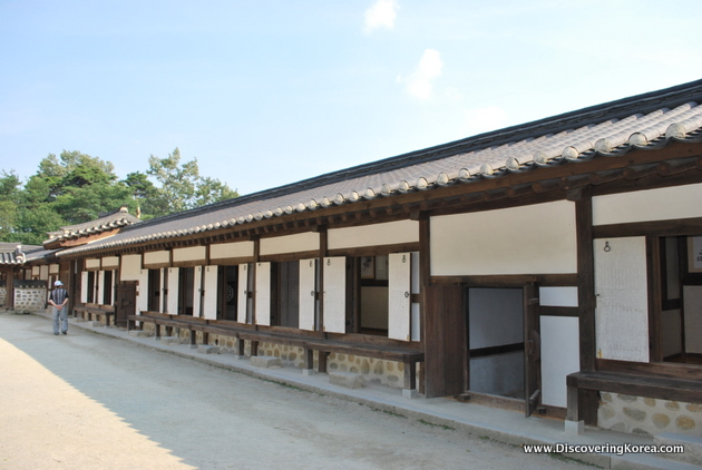 A long low building with dark wood frame and white panels in between. A traditional curved roof in a dark color, in front of the building is a concrete courtyard.