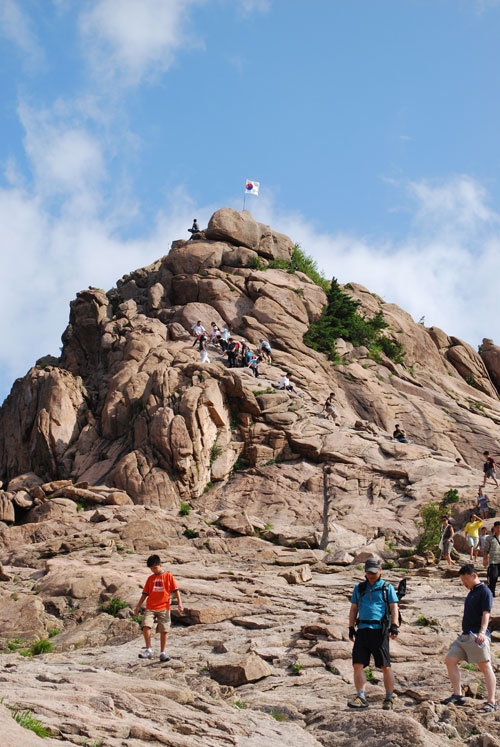 A large rocky outcrop with a Korean flag at the top, people in the process of scrambling up it, and others walking away from it. The background is blue sky with wispy clouds and bright sunshine.