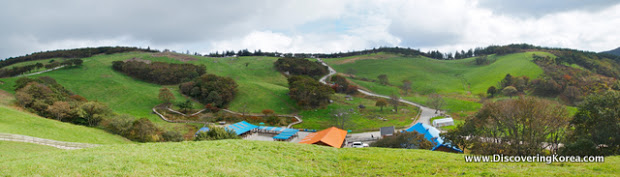 A panoramic view of lush green pasture with blue and orange roofed buildings in the center of the frame and clouds in the background.