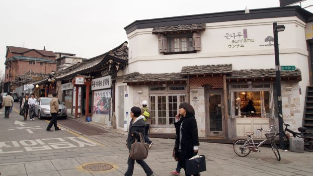 A street view of Samcheong dong neighborhood in Seoul. A pedestrian area with people walking, with the main street to the left of the frame. In the background is a white and gray building with a bicycle parked outside it, and various shop fronts extending down the main street.