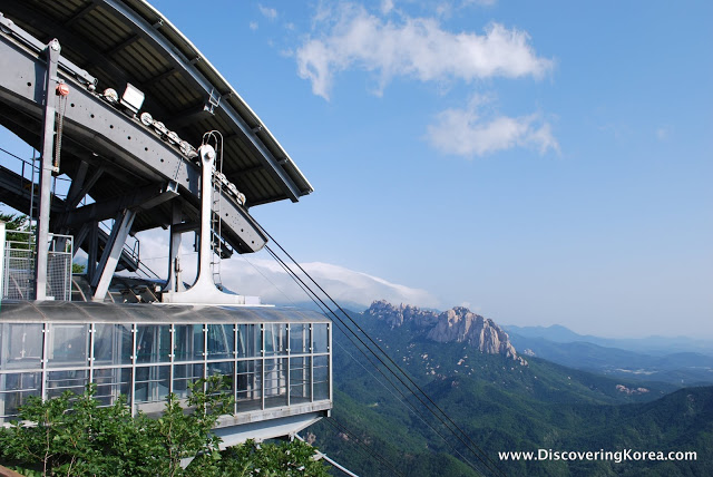 On the left of the frame is the top of a cable car on Seoraksan in Korea. Looking into the distance are rocky crags and mountains with a blue sky and wispy clouds.