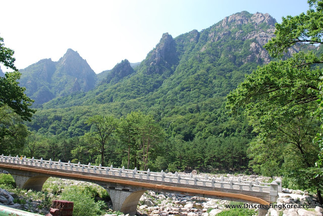 A pedestrian bridge over a rocky stream in Seoraksan, with a view over rocky outcrops covered in lush vegetation in bright sunshine.