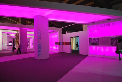 A view into a large expansive room with columns brightly lit in pink light.