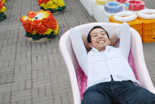 A man wearing a pink striped shirt and jeans reclines in a pink chair with colorful plastic boxes and fake flowers behind. The background is a concrete brick surface.
