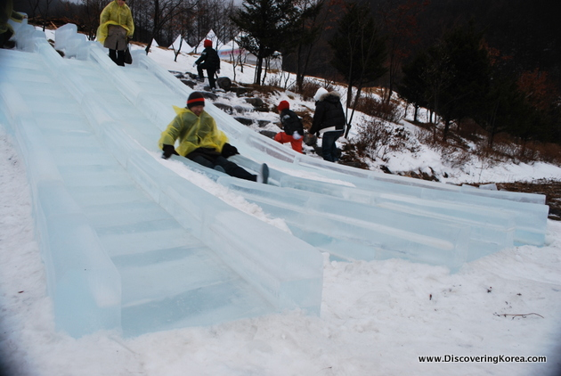 Transparent slides set amongst the snow at Taebaeksan snow festival in Korea. People dressed in yellow waterproof jackets are sliding down, with others walking up stairs to the top.