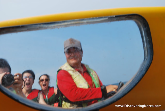 A man seen through the side window of a yellow speedboat. His hands on the steering wheel and in the background three people one of whom is taking a photograph.